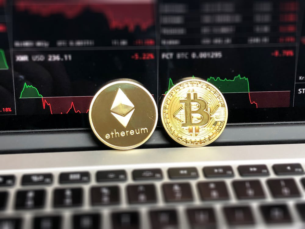 Ethereum and bitcoin placed on laptop