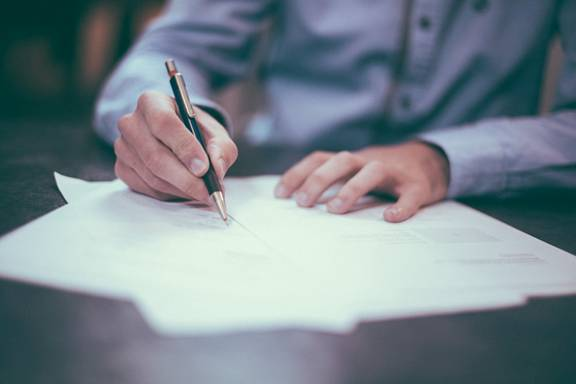 A person signing a contract with a black pen