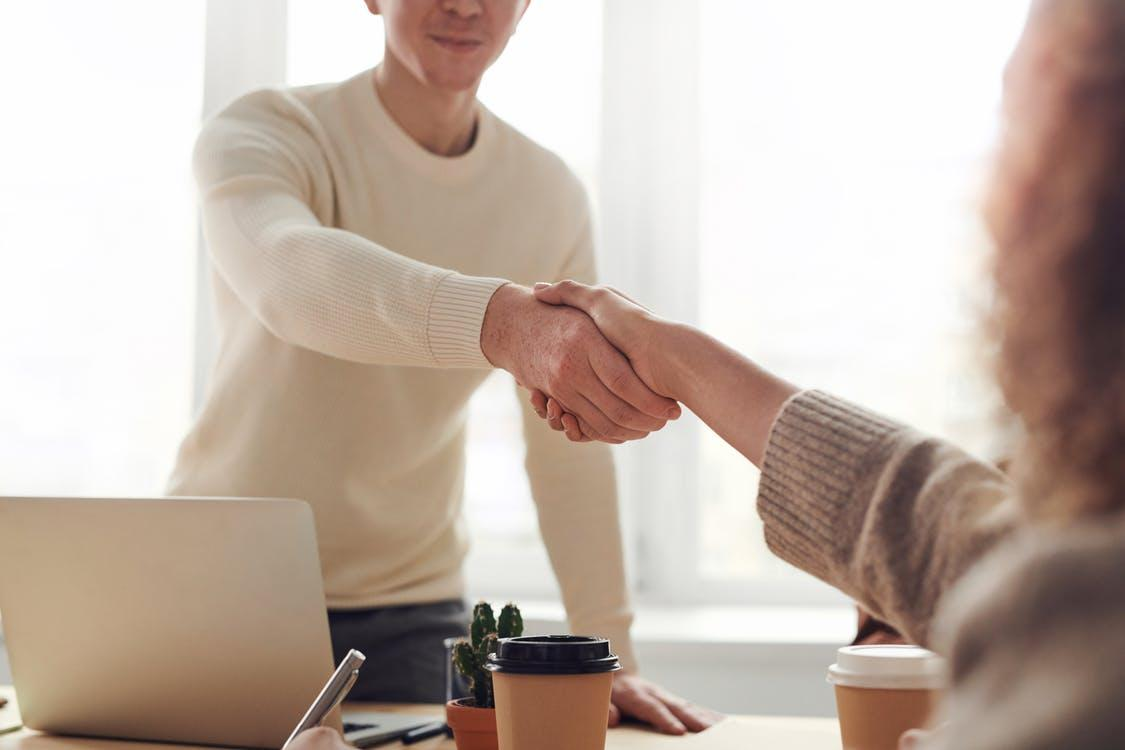 A man and woman shaking hands across the table