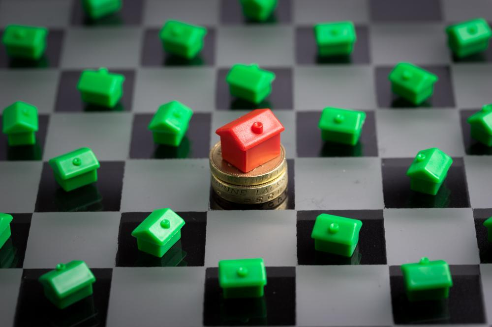 Model homes on a chessboard and some coins, a real estate marketing concept.