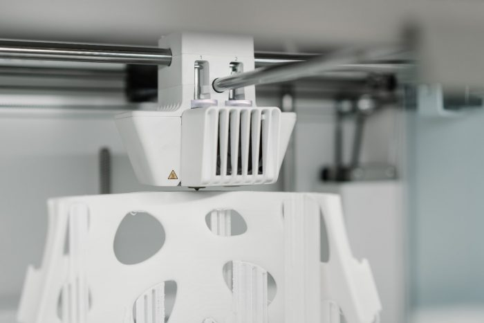 A 3D printer printing a cast out of white plastic-like material